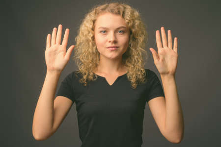 Young beautiful woman with curly blond hair against gray background Stockfoto