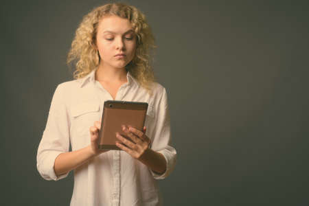 Young beautiful businesswoman with curly blond hair against gray background