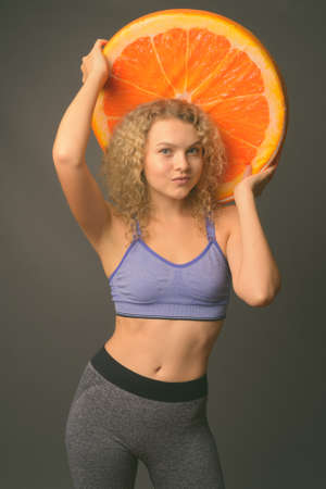 Young beautiful woman with curly blond hair ready for gym against gray background