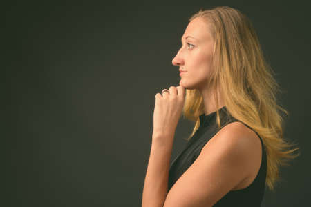 Young beautiful businesswoman with straight blond hair against gray background Reklamní fotografie