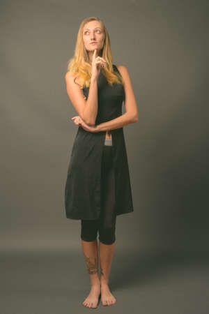 Young beautiful woman with straight blond hair against gray background