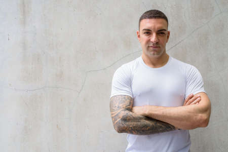 Handsome man with tattoos against concrete wall Reklamní fotografie