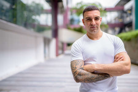 Portrait of handsome man with tattoos in the city outdoors