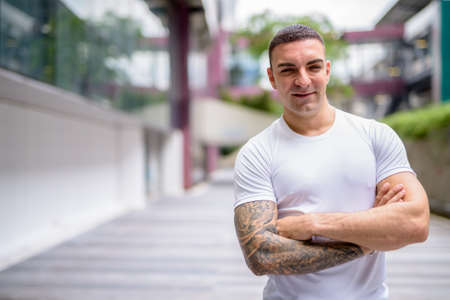 Happy handsome man with tattoos smiling in the city Reklamní fotografie