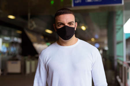 Portrait of man wearing mask and social distancing at the sky train station