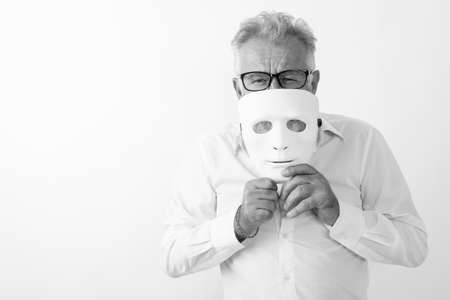 Studio shot of handsome senior bearded man covering mouth with white mask while wearing eyeglasses against white background