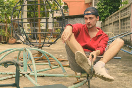 Young bearded man thinking while sitting at old rusty merry go round and wearing cap in the old playground
