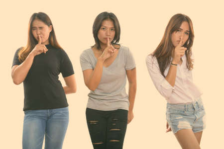Studio shot of three young Asian woman friends with finger on lips