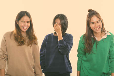 Studio shot of three happy young Asian woman friends smiling and laughing together