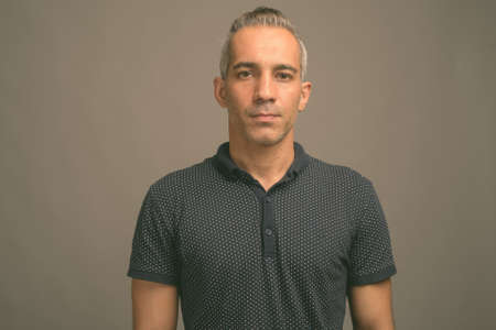 Handsome Persian man with gray hair against gray background 免版税图像