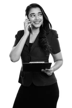 Thoughtful happy Indian businesswoman smiling while holding clipboard and talking on mobile phone