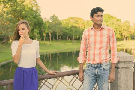 Multi ethnic couple thinking while looking sad on the bridge of peaceful green park