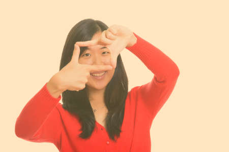 Young happy Asian woman focusing with fingers