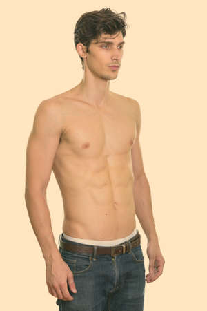 Studio shot of young handsome man standing and looking at right shirtless