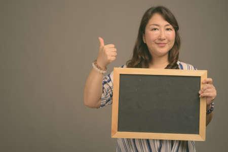 Mature beautiful Asian businesswoman against gray background Stock fotó