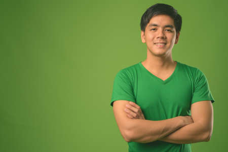 Young handsome Filipino man against green background Stock Photo