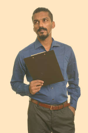 Young Indian businessman holding clipboard while thinking Stockfoto
