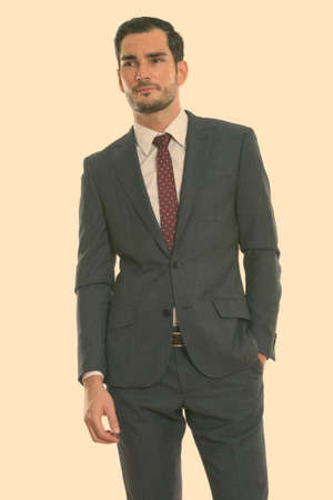 Studio shot of young handsome businessman standing while thinking with hand on pocket Foto de archivo