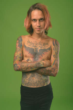 Studio shot of rebellious young man shirtless against green background