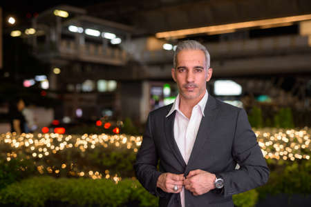 Portrait of handsome businessman wearing suit in city at night 免版税图像