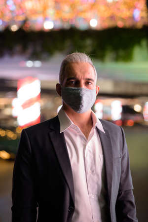 Businessman wearing suit and protective facial mask in city at night