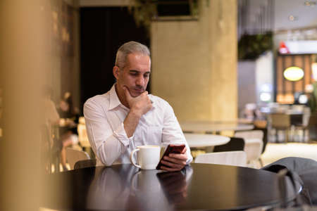 Businessman sitting in coffee shop while thinking and using phone 免版税图像