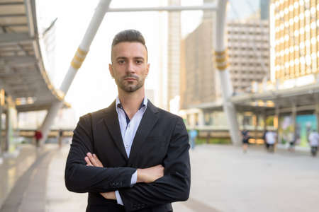 Portrait of handsome young businessman outdoors in city with arms crossed 免版税图像
