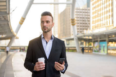 Businessman outdoors holding coffee cup and mobile phone 免版税图像