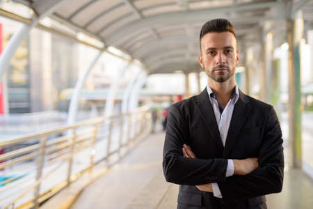 Confident businessman outdoors in city with arms crossed