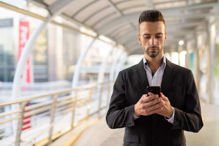 Italian businessman outdoors in city using mobile phone