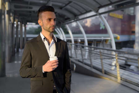 Businessman outdoors in city holding coffee cup while thinking 免版税图像