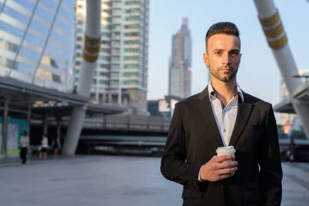 Portrait of handsome young businessman outdoors in city holding coffee cup
