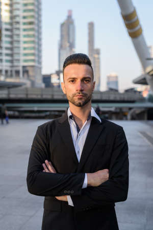 Handsome young businessman outdoors in city with arms crossed