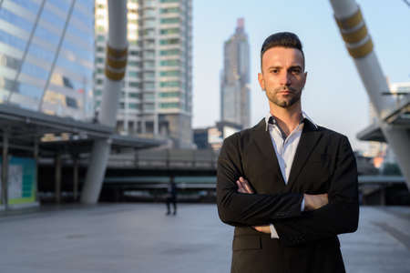 Handsome young businessman outdoors in city looking at camera
