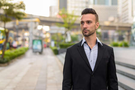 Portrait of handsome young businessman thinking outdoors in city