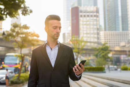 Portrait of handsome young businessman outdoors in city using phone