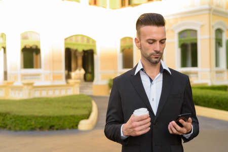 Businessman using phone and holding coffee cup outdoors 免版税图像