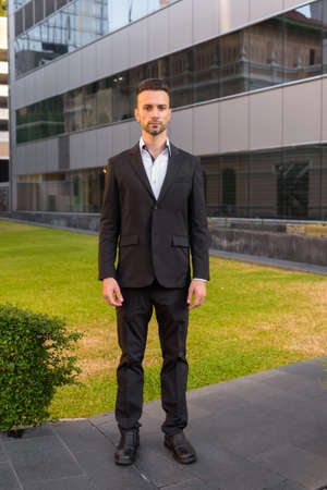 Full length shot of businessman standing outdoors wearing suit