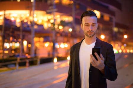 Portrait of young businessman against a city by night Reklamní fotografie
