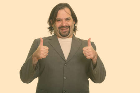 Happy fat Caucasian businessman smiling and giving thumbs up