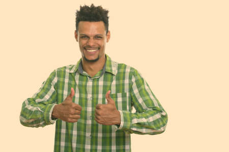 Studio shot of young happy African man smiling while giving thumbs up