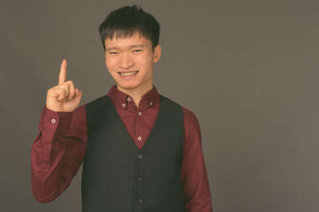Young Chinese businessman against gray background