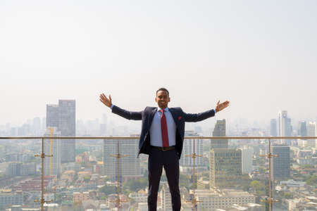 Portrait of handsome young African businessman wearing suit with arms raised in the rooftop with city background Banco de Imagens