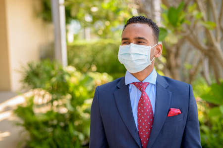 African businessman with surgical medical mask for protection while thinking outdoors