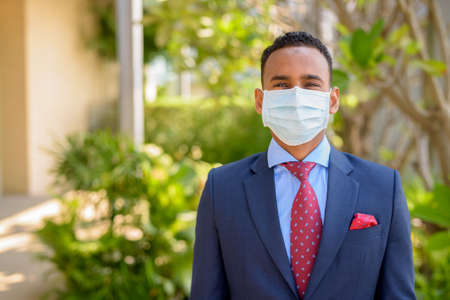 African businessman with surgical medical mask for protection outdoors
