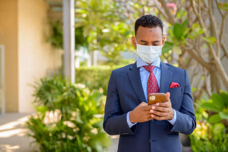 African businessman with surgical medical mask for protection and using mobile phone outdoors