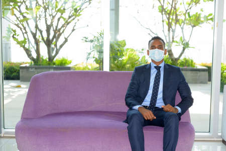 African businessman wearing face mask and sitting on sofa at modern office Banco de Imagens