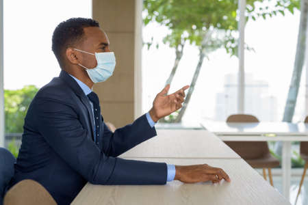 African businessman with surgical medical mask for protection sitting at office while talking Banco de Imagens