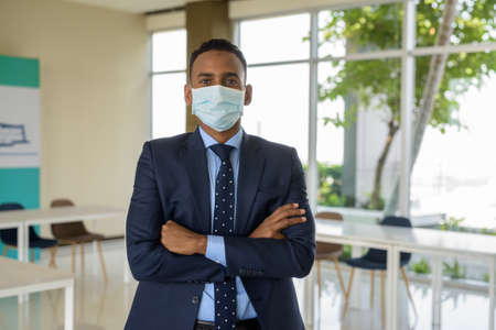 African businessman with surgical medical mask for protection with arms crossed at office looking at camera with arms crossed