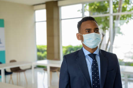 African businessman with surgical medical mask for protection thinking at office Banco de Imagens